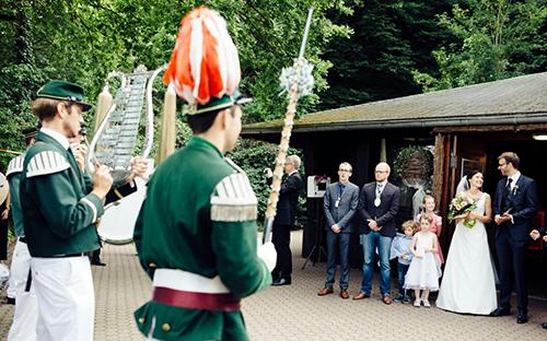 Das Brautpaar, Majestät Robin Grießel und Hauptmann Johannes Schütz lauschen dem Ständchen unter er Leitung von Tambourmajor Nils Henscheid (v.r.n.l.). Foto: Max Brunnert