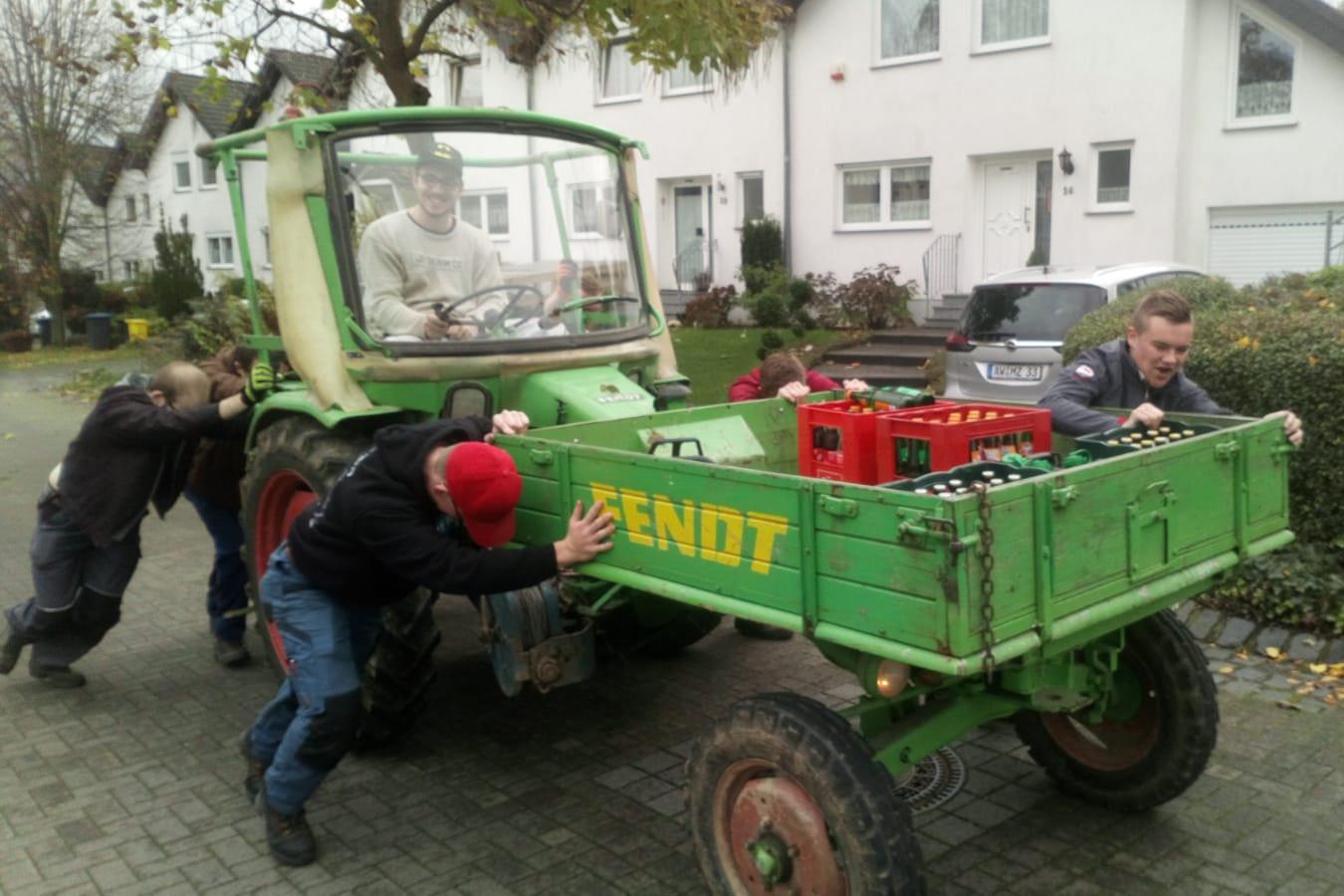 Um den Traktor ans Laufen zu bringen, schieben die Junggesellen den Traktor an, während Majestät Markus Fabritius versucht, den Motor zu starten. Foto: JSG